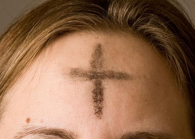 Ash cross on woman's forehead